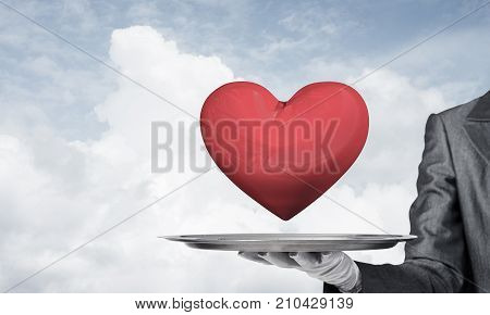 Cropped image of waitress's hand in white glove presenting big red heart on metal tray with cloudy skyscape on background.