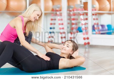 Shot of a mature woman fitness instructor helping her young female client exercising at the gym abdominal fat weight loss beauty healthcare positivity wellness wellbeing concept.
