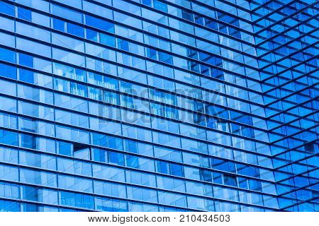 Abstract shot of glass transparent skyscraper office building for texture or background. Blue toned