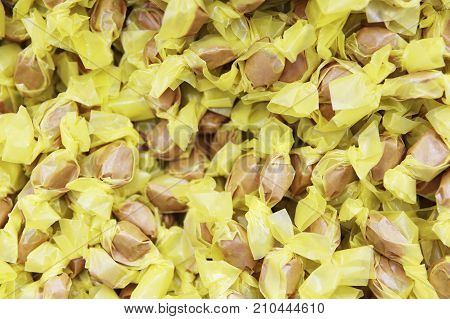 background of yellow wrapped candies. texture of salt water taffy