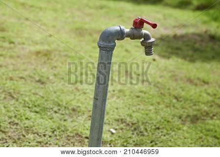 A tap with green grass background / Water consumption and usage concept