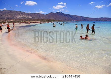 CRETE, GREECE - JULY 21, 2016: People on pink sand beach with azure clear water of famous Elafonisi (or Elafonissi), Crete island, Greece.
