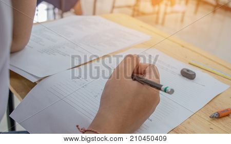 Students using pencil writing information on white answer paper in high school Asian exams room Tests or examination is assessment intended to measure knowledge skill aptitude Education Concept