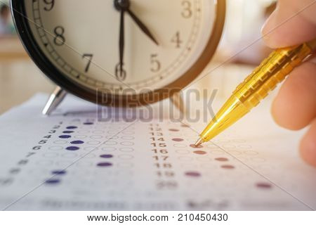 Students taking optical form of standardized exams near Alarm clock with hands holding yellow pen for final examination in school college university classroom Education concept