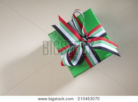 UAE National Day charity - a concept. Small gift box tied with ribbon with UAE national colors.