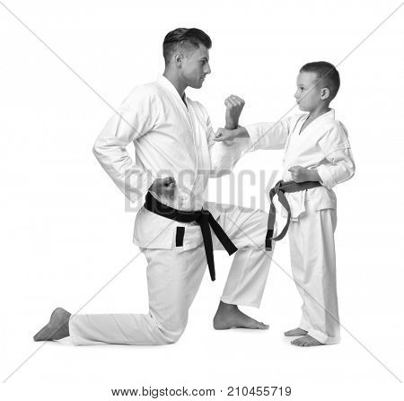 Little boy with teacher practising karate on white background