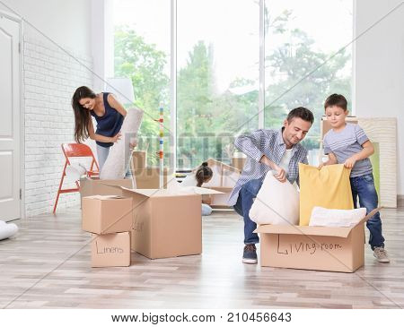 Happy family unpacking moving boxes in room at new home