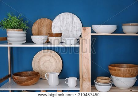 Kitchen shelving with dishes on blue wall background