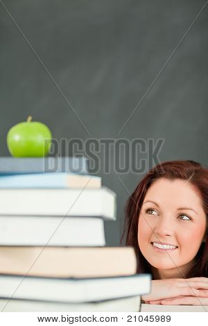 Portrait Of A Young Student Looking At The Apple On The Top Of Her Books