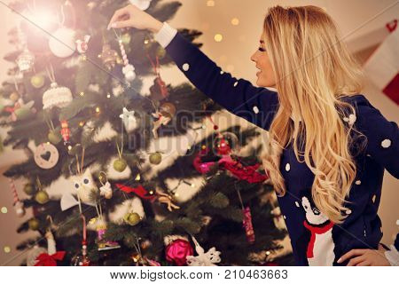 Happy beautiful young woman decorating christmas tree
