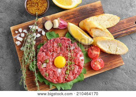 Delicious steak tartare with yolk on wooden board
