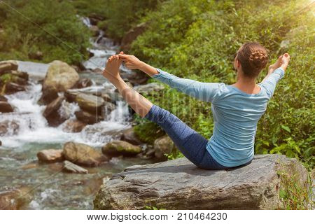 Woman doing Ashtanga Vinyasa asana Upavistha Konasana outdoors at tropical waterfall