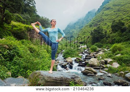 Yoga outdoors - woman doing Ashtanga Vinyasa Yoga balance asana Utthita Hasta Padangushthasana - Extended Hand-To-Big-Toe Pose position posture outdoors at waterfall