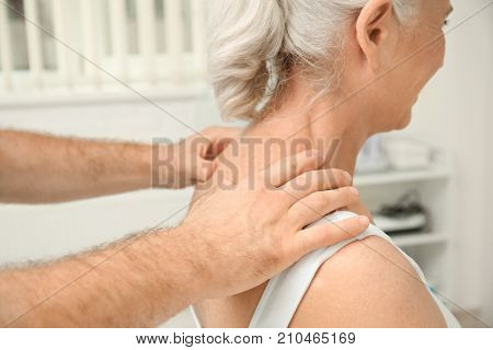 Elderly woman getting shoulder massage at physical therapy office