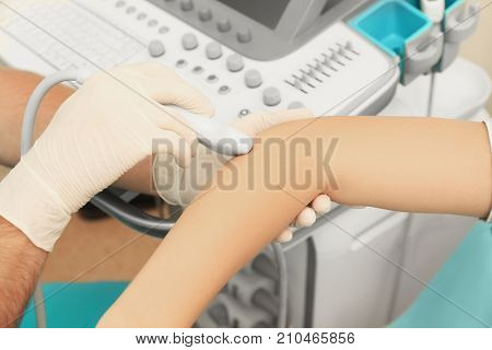 Doctor conducting ultrasound examination of patient's elbow in clinic