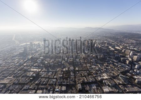 Aerial view of sunshine, smog and urban downtown Los Angeles streets and buildings.