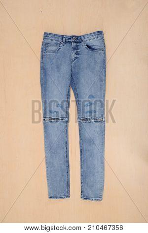 blue denim jean hanging on wooden texture