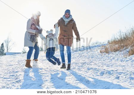 Family with child playing in the snow together in winter