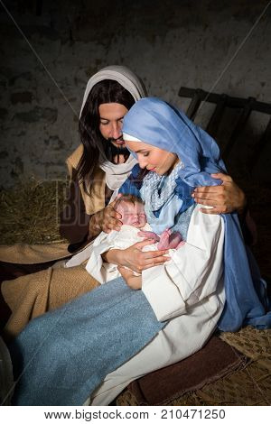 Live Christmas nativity scene in an old barn. Reenactment play with authentic costumes.  The baby is a property released doll.