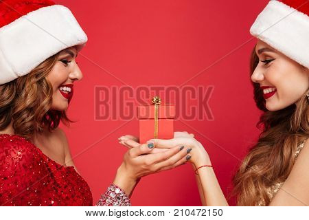 Close up portrait of two happy smiling women in christmas hats holding a gift box and looking at each other isolated over red background