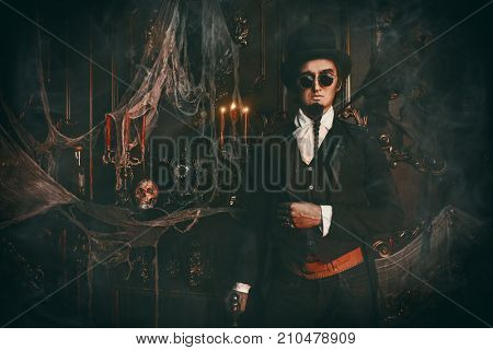 Halloween. Elegant and mysterious gloomy man aristocrat in a black tailcoat and top-hat stands in an old abandoned castle. The Dark Lord. Vampire man.