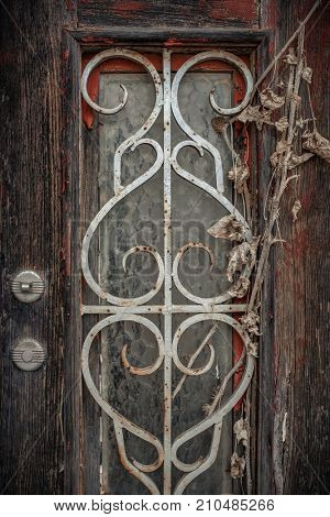 Detail of old textured wooden door with window in an abandoned house