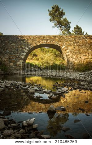 Ancient bridge over an almost dry river in Portugal