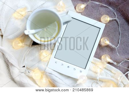 Ebook, cup and electric garland on textile background with free copy space