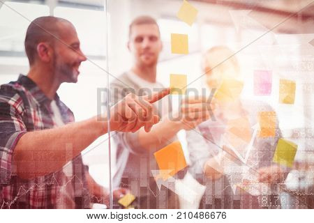 Stocks and shares against business people sticking adhesive notes in office