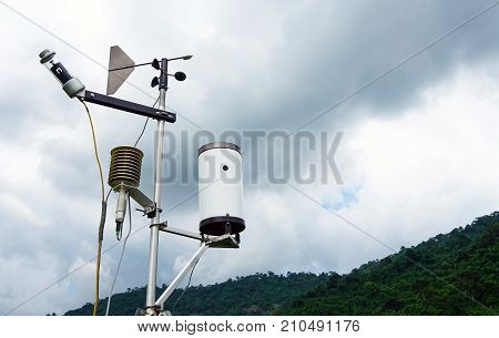 Meteorological weather station antenna with meteorology sensors pale overcast cloudy sky and forest in background. Weather station for background.