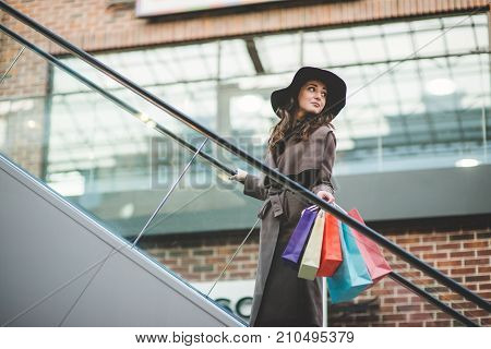 Young smiling woman with shopping bags in shopping center