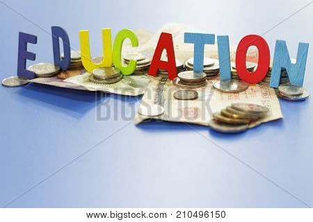 Word EDUCATION on blue background with coins and money. Concept of education and financial.