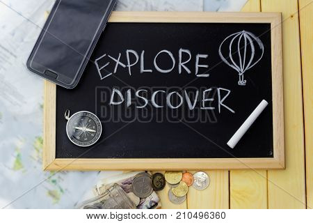 Travel and leisure concept. Smartphone, compass,money spilling out from glass jar, blurred map,chalk and black board with word EXPLORE AND DISCOVER on wooden table
