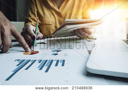 Business Meeting Time. Business Woman Holding Notepad And Pencil Pointing At Business Financial Repo