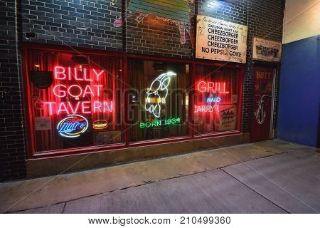 Chicago IL - July 15 2017: Famous scene downtown Chicago. The iconic Billy Goat Tavern sign welcomes into the dark Lower Wacker underpass beneath the upscale Michigan Avenue shopping district.