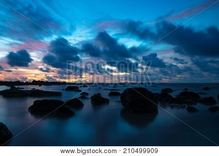 Sunset at Koh Lanta with Stones in the sea and Phi Phi islands in the horizon with long exposure, Koh Lanta, Thailand, Asia