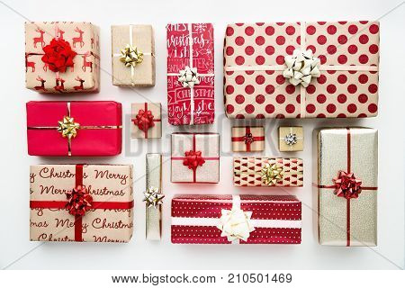 Collection of Christmas presents arranged on a white background, overhead view