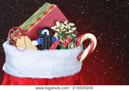 Closeup of a Christmas Stocking filled with toys, presents and a candy cane. Horizontal format with copy space and snow effect.