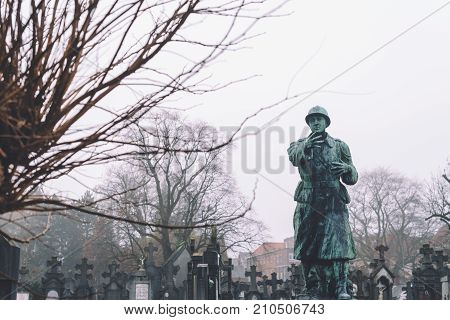 December, 29th, 2016 - Ghent, East Flanders, Belgium. Stone cemetery statue of a soldier man and tomb crosses on Campo Santo historical old graveyard in Sint-amandsberg municipality, Gent.