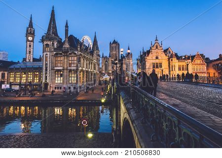 Ghent, Belgium - December 27th, 2016. Saint Michael's bridge panoramic view with merchant houses on Graslei street, Saint Nicholas church and Clock Tower. Gent Old town by Christmas evening lights.