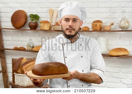 Horizontal shot of a handsome bearded young professional baker in uniform posing at his bakery with a loaf of delicious freshly baked bread profession occupation salesperson small business.