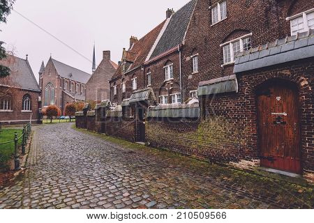 Ghent, Belgium - January 1th, 2017. New Saint Elisabeth beguinage in Sint-Amandsberg district. Groot Begijnhof Sint-Amandsberg. Brick belgium houses, cobbled street and wall by autumn in Gent.