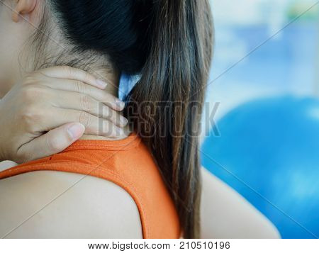 Young fitness woman having neck pain after exercise with fitness ball background.