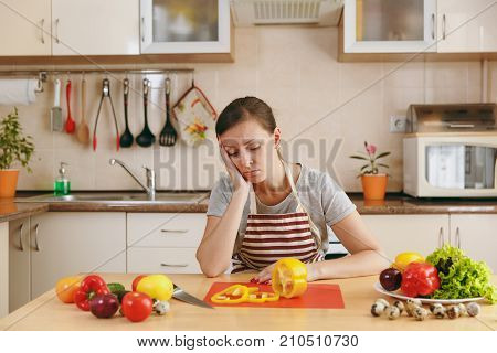 A Young Emaciated Tired Woman In An Apron Cooking In The Kitchen At Home. Dieting Concept. Healthy L