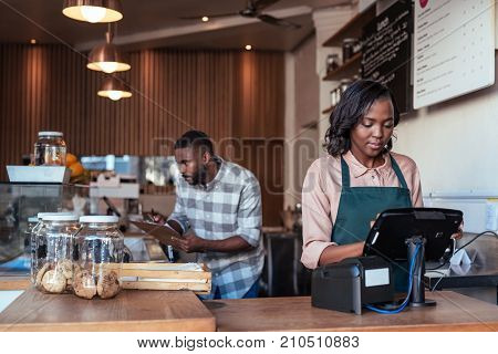 Young African entrepreneur working at the checkout counter of a trendy cafe with a coworker in the background
