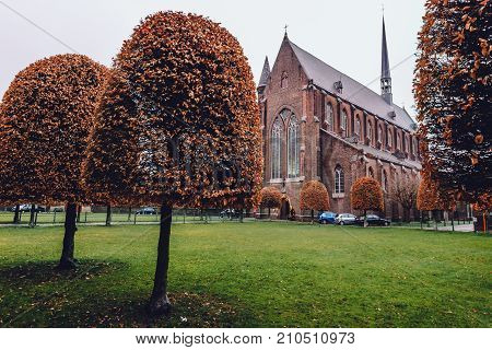 Ghent, Belgium - January 1th, 2017. Autumn park and church in New Saint Elisabeth beguinage in Sint-Amandsberg district, Gent. Known as Groot Begijnhof Sint-Amandsberg. Flanders World Heritage Site.