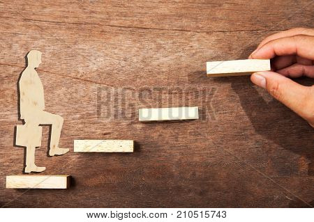 Personal development personal and career growth progress and potential concepts. Coach (human resources officer manager mentor) motivate employee to growth. Wooden blocks and businessman