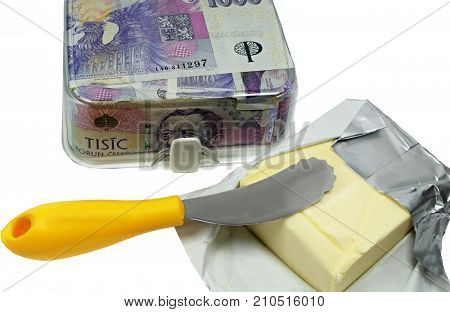 The expensive butter/Butter churn full of Czech banknotes and unpacked butter with yellow butter knife.
