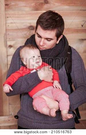 Young father holding son against wooden background. Vertical shot
