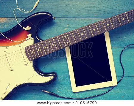 Music concept image vintage guitar with earphones on a rustic wooden background Jazz rock or blues music concept